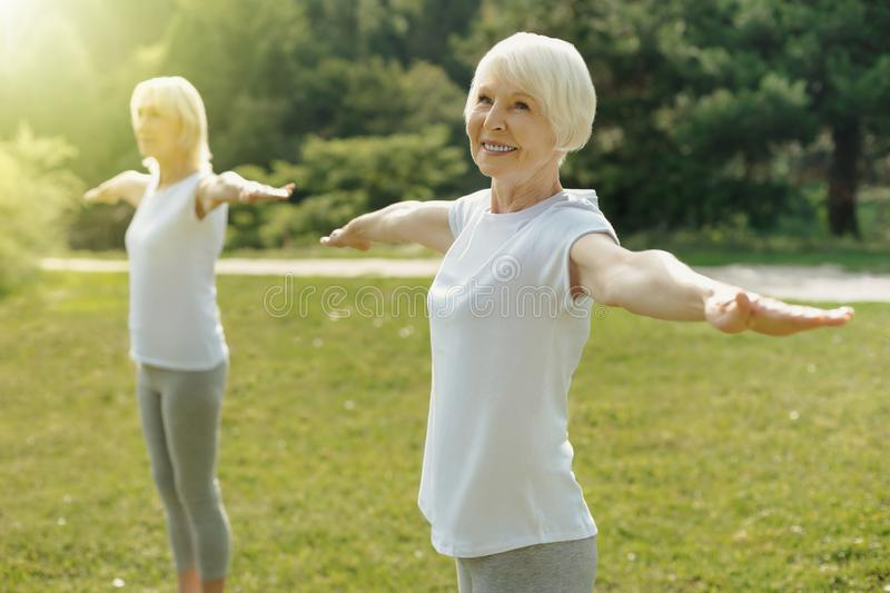 Beaming retired woman standing with her arms outstretched royalty free stock photos