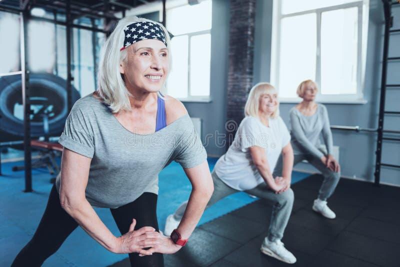 Beaming senior lady taking group training at gym stock image