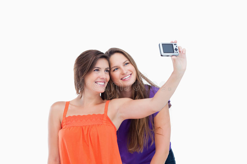 Beaming teenager photographing herself and a riend royalty free stock images