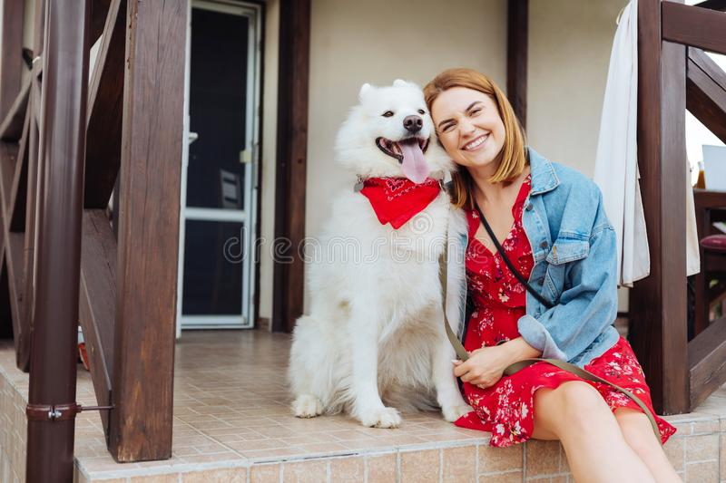 Beaming woman coming to summer house with her dog stock photos