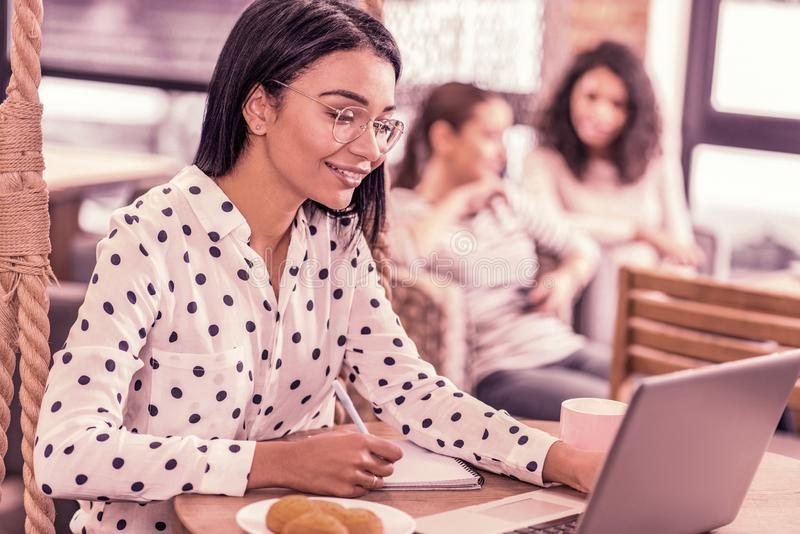 Beaming woman wearing spotted blouse looking at her laptop reading message stock photography