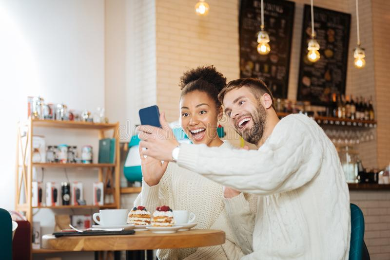 Beaming young couple making funny selfie together stock photos