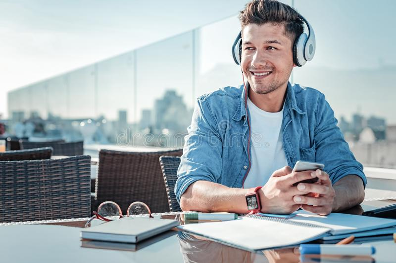 Beaming young man sitting on terrace and listening to music stock photo