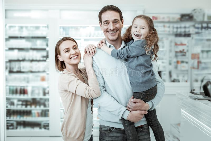 A beamingly smiling family sharing cuddles near the pharmacy checkout royalty free stock photo