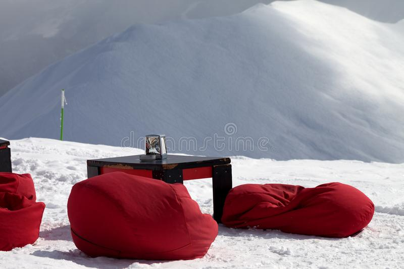 Bean bag chairs and table in outdoor cafe at ski resort royalty free stock image