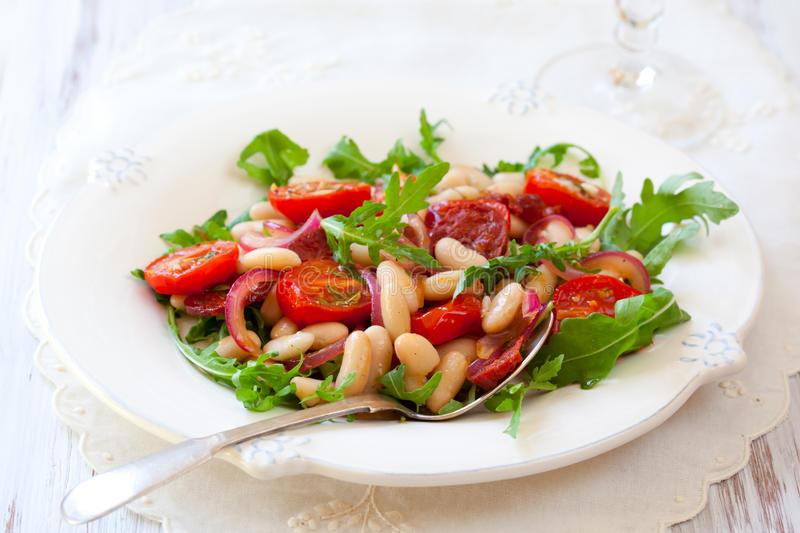 Bean salad. Cannellini bean salad with roast cherry tomatoes,chorizo and red onion royalty free stock photography