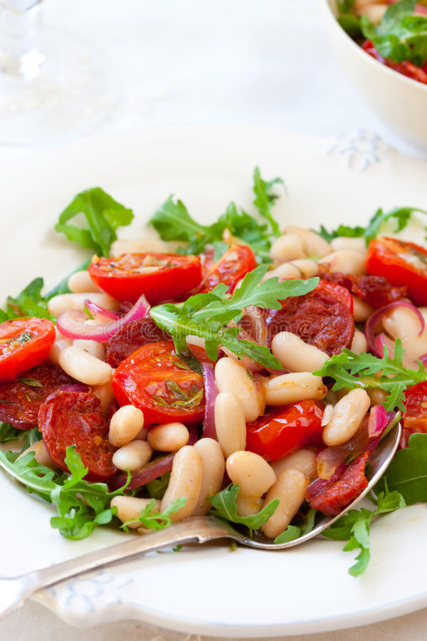 Bean salad. Cannellini bean salad with roast cherry tomatoes, chorizo and red onion stock image