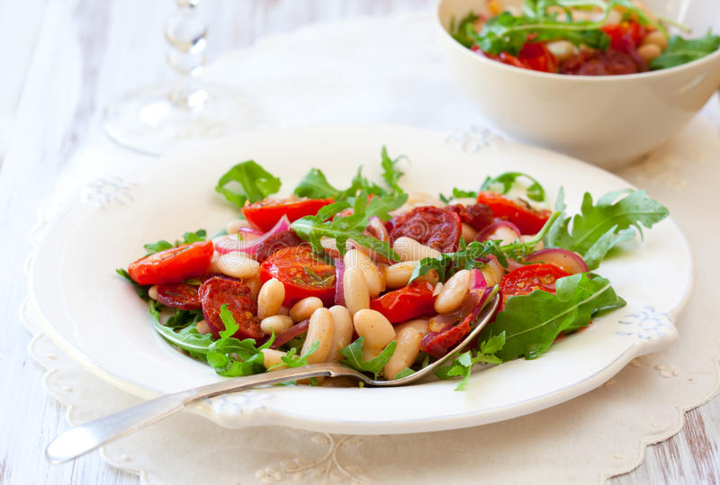 Bean salad. Cannellini bean salad with roast cherry tomatoes,chorizo and red onion royalty free stock photo