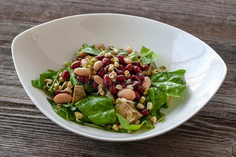 Bean salad with vitamins. Salad with spinach, arugula, avocado royalty free stock photos