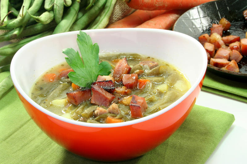 Bean stew. Bean soup with roasted bacon and lovage royalty free stock image