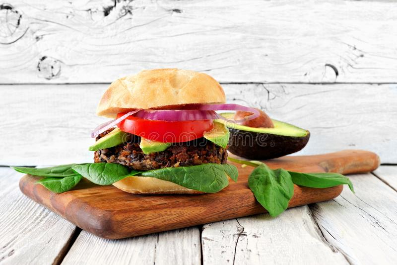 Bean and sweet potato veggie burger against rustic white wood royalty free stock photo