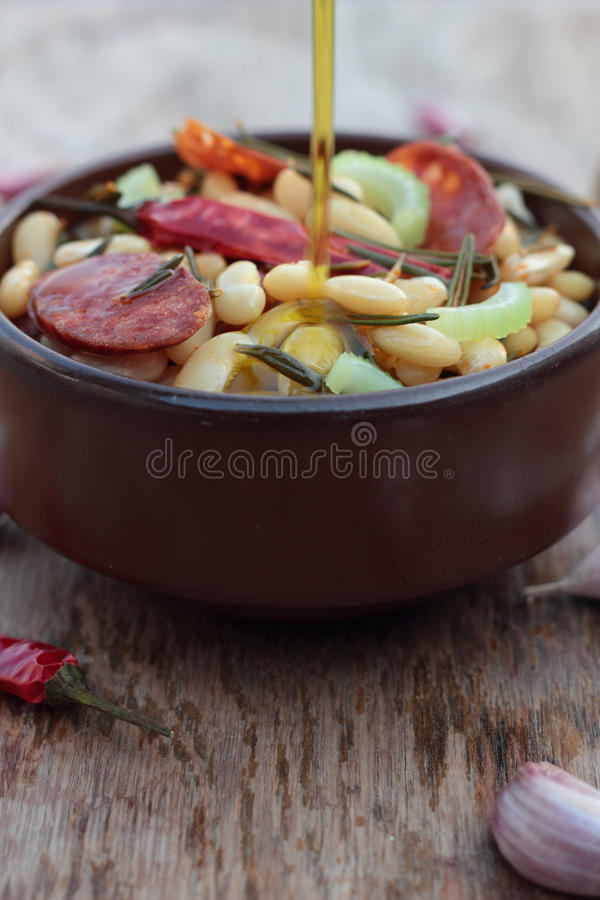 Beans and chorizo. Beans and chorizo cooked with vegetables and rosemary leaves royalty free stock image