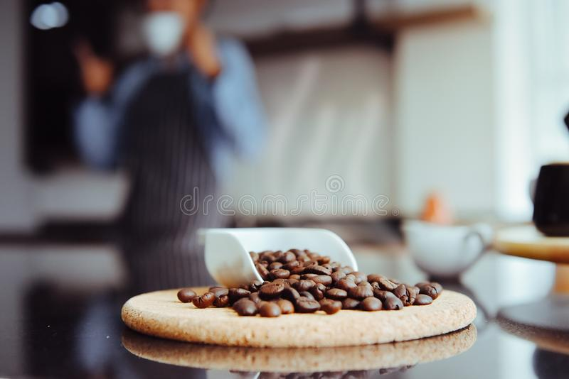 Beans coffee on the table. With blur asian barista women royalty free stock photo