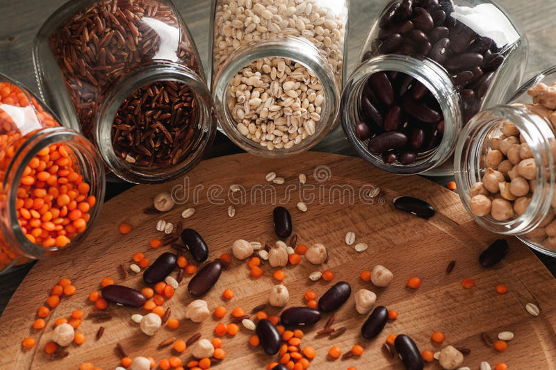 Beans and grain in glass jars on a wooden table royalty free stock images