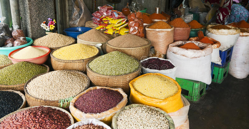 Beans and Grains. A colorful assortment of dried beans and grains with bright red crushed peppers in the background for sale at a market in Hue, Vietnam royalty free stock photo