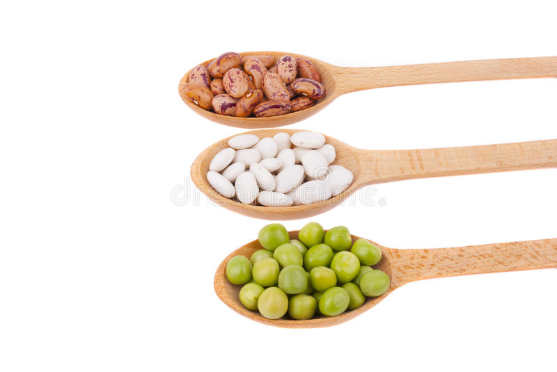 Beans and green peas in a spoon royalty free stock photography