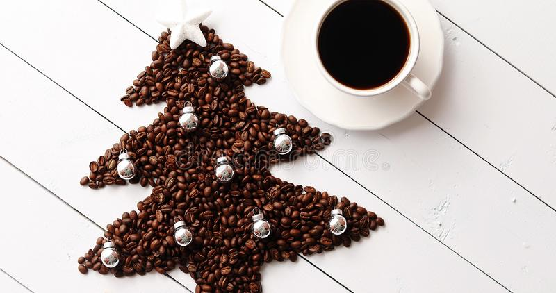 Beans in shape of fir and cup of coffee royalty free stock photo