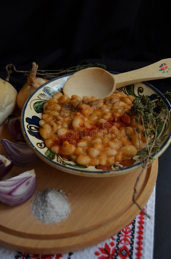 Beans stew with thyme and paprika. Beans stew, thyme, onion, bread and salt. Food for your soul royalty free stock photo