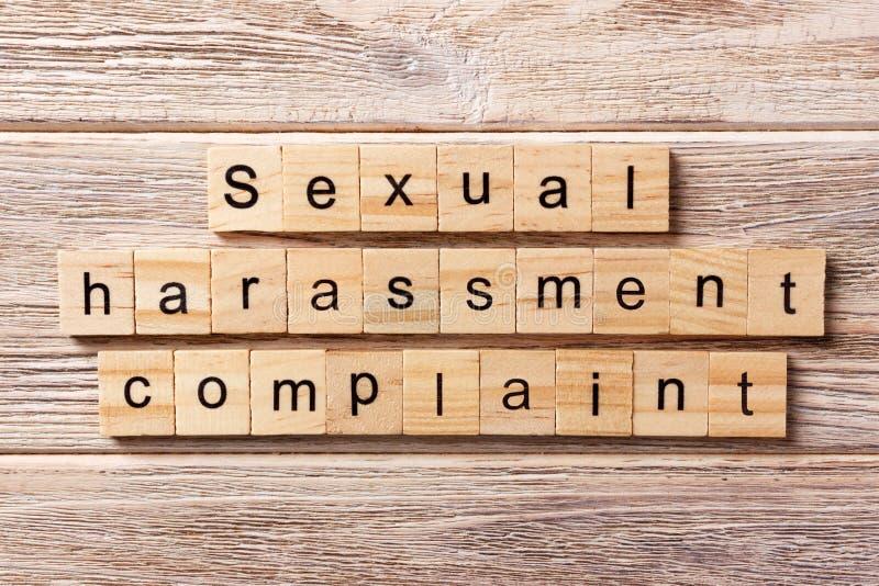 Beanstandungswort der sexuellen Belästigung geschrieben auf hölzernen Block Beanstandungstext der sexuellen Belästigung auf Tabel stockfotografie