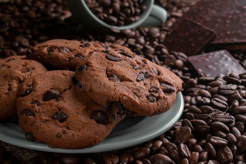 Кофейные зерна с шоколадом и печеньями в чашке и плите стоковое изображение rf