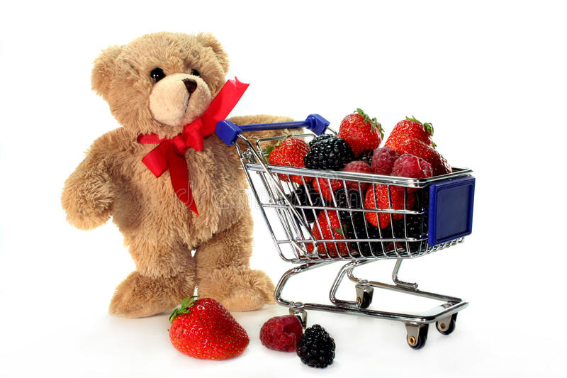 Bear and Berries. Teddy with shopping carts, laden with delicious berries royalty free stock photos