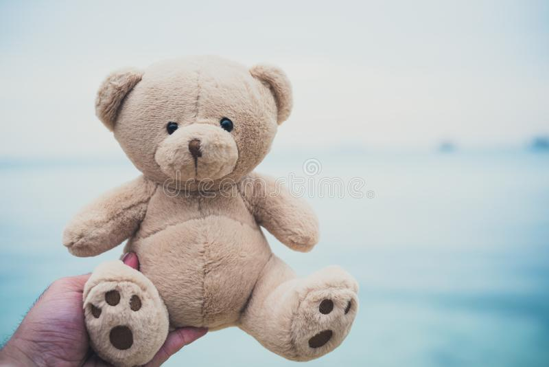 Bear doll in hands. Beach and sea background. Childhood and past memory concept. Happiness and lifestyle concept. Toy and soulmate. Theme. Dark ton film filter royalty free stock photography
