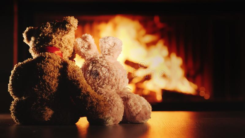 Bear and rabbit in a hug sit by the fireplace. Valentine`s Day concept stock images
