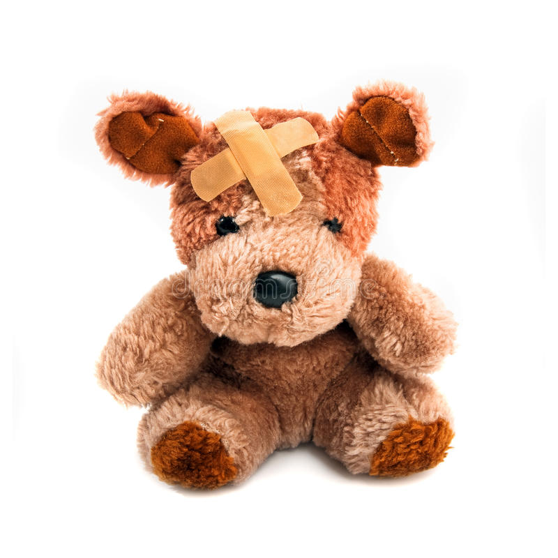 Bear Toy. Cute little bear toy with plaster on his head over a white background royalty free stock images