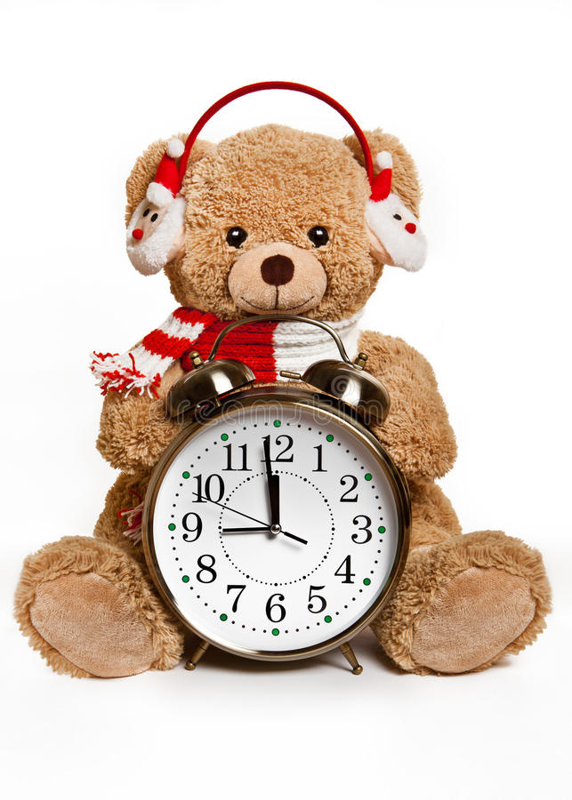 Bear toy with alarm clock on white background. Teddy bear alarm clock with headphones on white background royalty free stock images