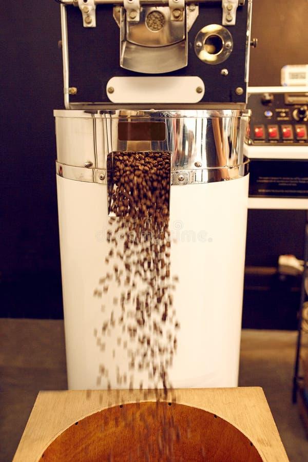 Bearbeiten Sie für den Bratkaffee maschinell, der gebratene Bohnen in zuführt stockfotografie