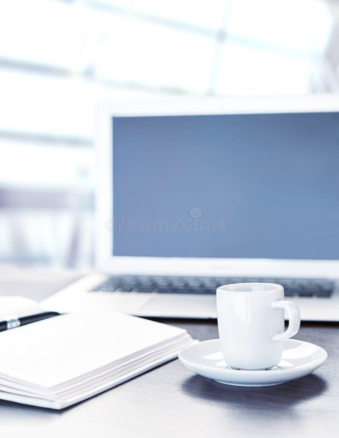 Bearbeiten Sie Schreibtisch mit einem Tasse Kaffee-Computerlaptop, Notizbuch, Stift lizenzfreies stockfoto