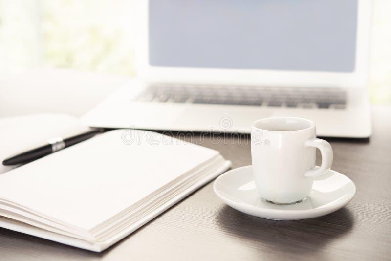 Bearbeiten Sie Schreibtisch mit einem Tasse Kaffee-Computerlaptop, Notizbuch, Stift stockfoto