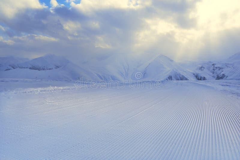 Bearbetat snowcatspår, band på snö royaltyfria foton