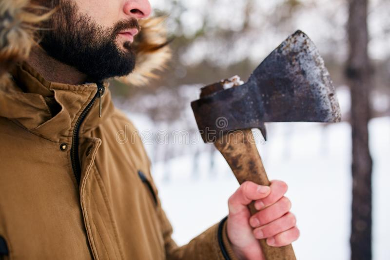 Beard and axe. Lumberjack standing with weathered rusty axe in his hand. Close view, unrecognizable man in forest royalty free stock image