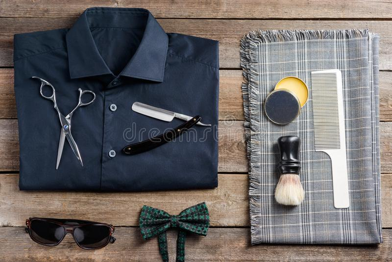 Beard comb and plaid scarf. Plaid scarf, a shirt, sunglasses, a bow tie, scissors, a straight razor, a beard comb, wax and a brush, a top-view image. Hipster royalty free stock photos