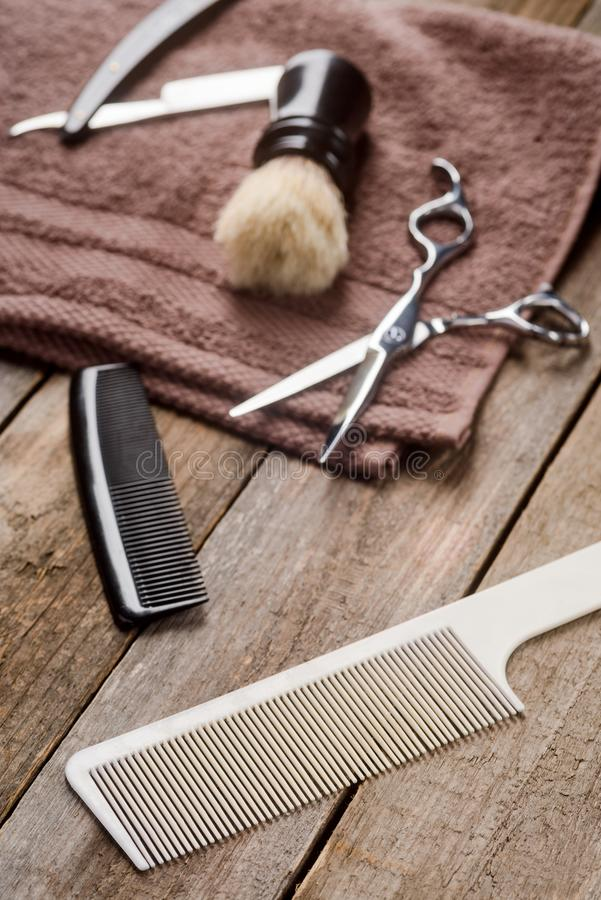 Beard comb and scissors. Beard comb, scissors, a brush, a towel and a straight razor on the wooden surface, close-up. Hipster grooming royalty free stock image