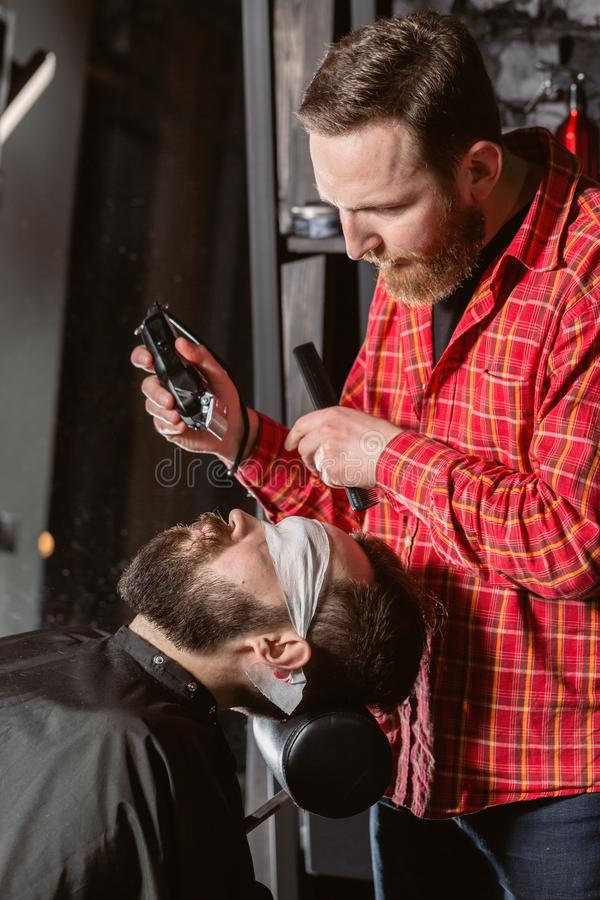 Beard cutting, face care. Barber work with clipper machine in barbershop. Professional trimmer tool cuts beard and hair. Barber work with clipper machine in royalty free stock images