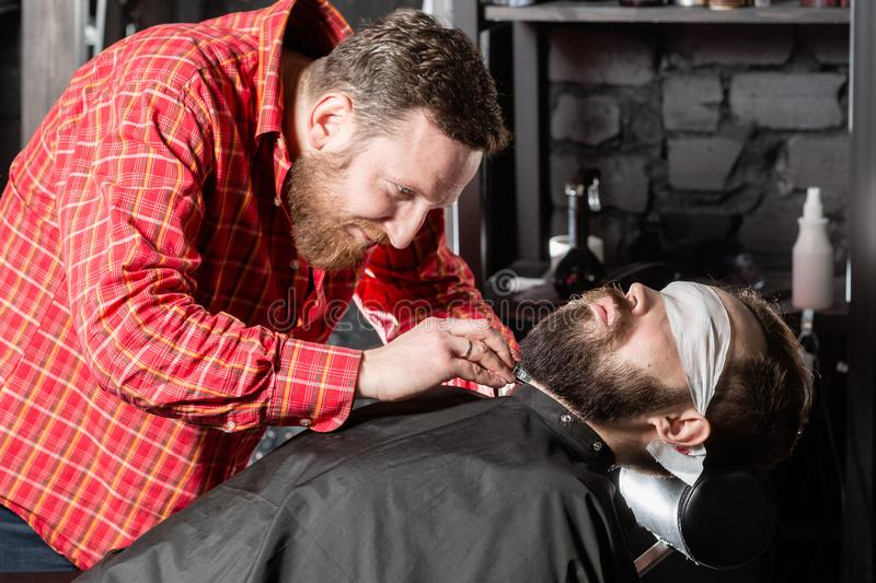 Beard cutting, face care. Barber work with clipper machine in barbershop. Professional trimmer tool cuts beard and hair royalty free stock image