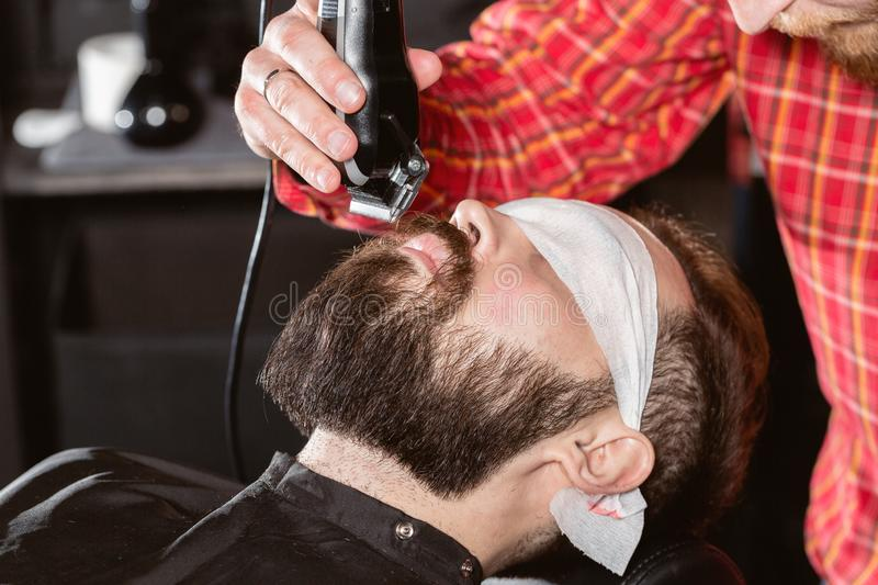Beard cutting, face care. Barber work with clipper machine in barbershop. Professional trimmer tool cuts beard and hair. Barber work with clipper machine in stock photo