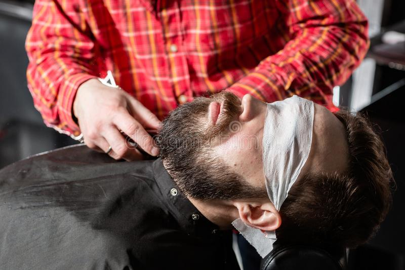 Beard cutting, face care. Barber work with clipper machine in barbershop. Professional trimmer tool cuts beard and hair. Barber work with clipper machine in stock photos
