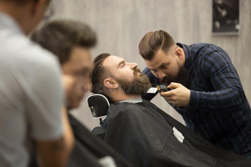 Beard grooming in hairsalon for men stock image