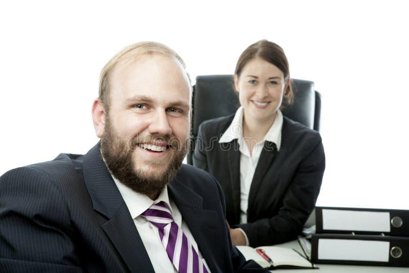 Beard man and woman at desk smiling