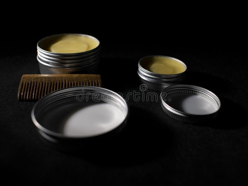 Beard and mustache wax and wooden comb on black background.  royalty free stock photo