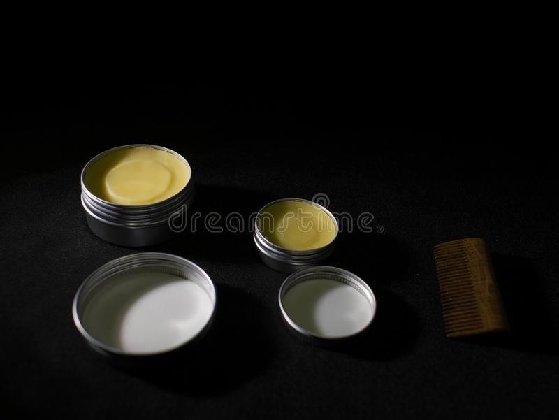 Beard and mustache wax and wooden comb on black background.  royalty free stock images