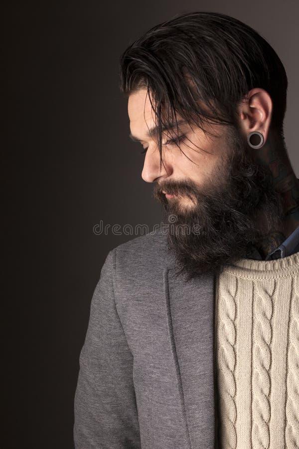 Beard and tatoos. Young man with long beard and tatoos posing in the studio royalty free stock photo