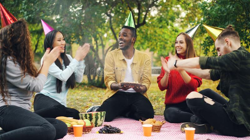 Bearded African American guy is having birthday party in park blowing candles on cake and laughing enjoying surprise royalty free stock photos