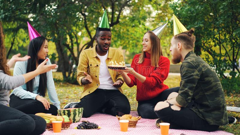 Bearded African American guy is having birthday party in park blowing candles on cake and laughing enjoying surprise. His friends are clapping hands sitting on royalty free stock images