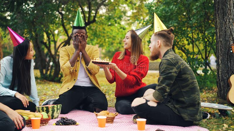 Bearded African American guy is having birthday party in park with candles on cake and laughing enjoying surprise. Sitting on blanket royalty free stock photography