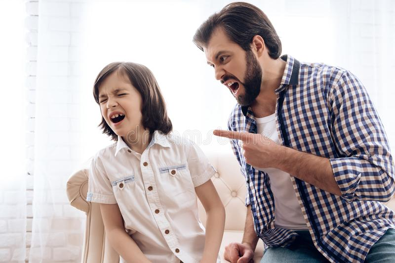 Bearded angry father scolds crying son. royalty free stock photos