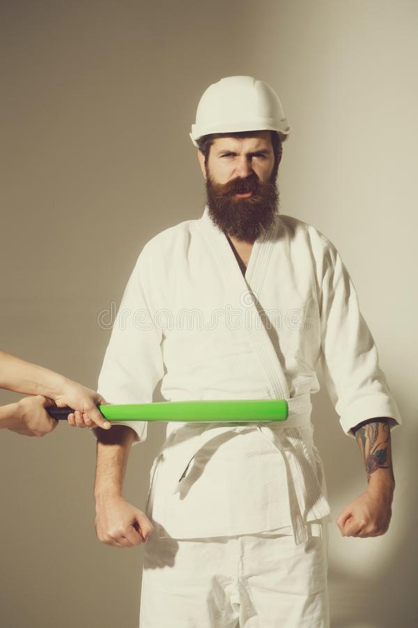 Bearded angry karate man in kimono, helmet with baseball bat stock photo